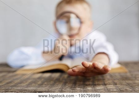 Little explorer. Amazing inventive dedicated kid playing with a lens and looking at his hands while reading a book