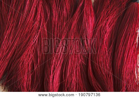 Red tassels background close up. Woman handicraft. Art, creativity, hobby, home workshop concept