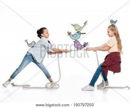 Girls pulling up rope with funny fairy birds sitting on it