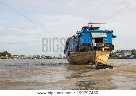A big cargo boat on the Mekong river at cloudy day in Mekong Delta southern Vietnam.
