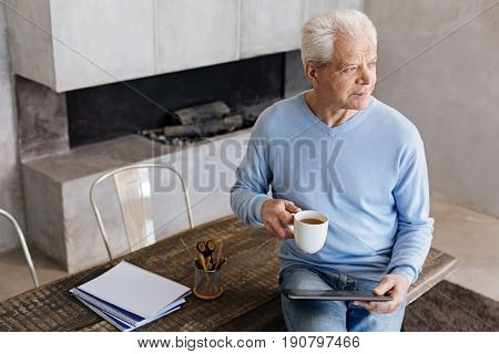 Still handsome. Cheery classy senior gentleman spending the beginning of a day in his home office while reading news and drinking coffee