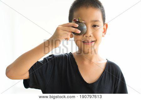 Asian boy shutting eyes with mangosteen isolated on white background