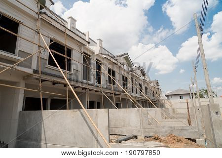 Rows of unfinished townhouses under construction with blue sky.
