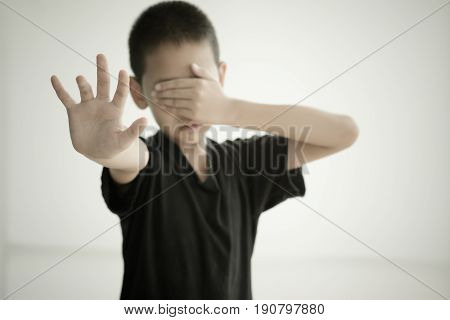 Stop abusing boy violence. child bondage Human Rights Day concept. Scared boy making a stop gesture