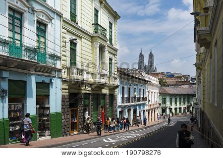 Quito Ecuador - January 30 2014: People in a street in the historic center of the city of Quito in Ecuador with the Basilica of the National Vow on the background.