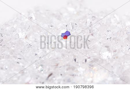Shiny glass beads on white background, one sparkling crystal. Jewelry, craft, bijouterie concept