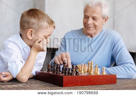 Strategic skills. Intelligent curios nice kid playing chess with his granddad and developing a winning strategy