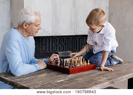 Caught in the process. Adorable excited hardworking boy sitting on a table and remembering how the chess pieces moving