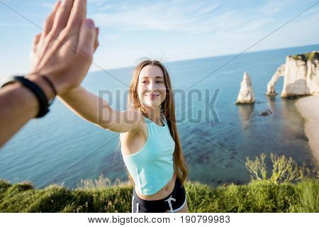 Happy playful woman in sportswear giving a five outdors on the rocky coastline background