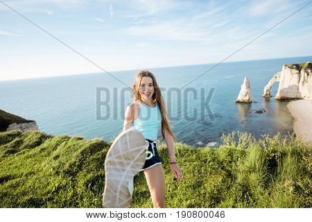 Young playful woman in sportswear kicking with leg outdors on the rocky coastline background