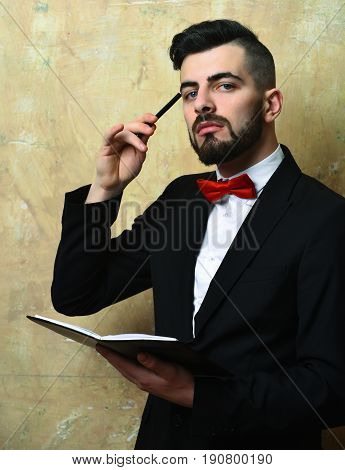 Young Insurance Agent With Neat Beard And Hairdo Reading Organizer