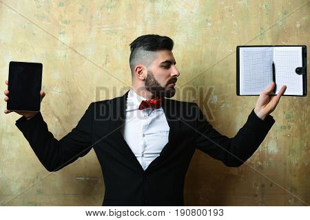 Stylish Boss With Neat Beard Holding Tablet And Empty Notebook
