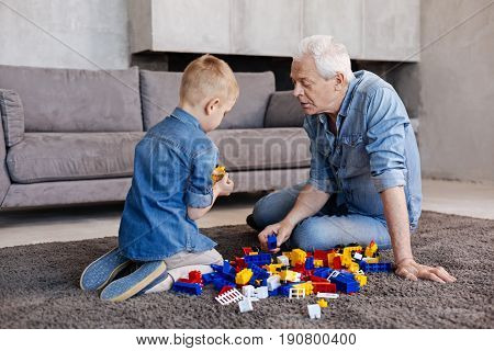 Building things. Nice original imaginative kid playing with a construction set while spotting something interesting and telling granddad about it