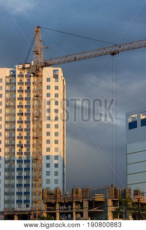 Old High-rise crane used in the construction of a multi-storey building raises the container with concrete in the light of the setting sun