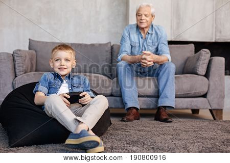 Both inspired. Adorable caring engaged grandpa sitting on a couch and observing the mastery of his grandchild while he enjoying new video game