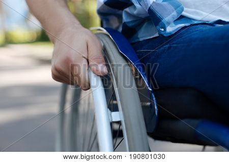 Paralyzed man. Young disabled male person sitting on his wheelchair looking forward while driving his machine
