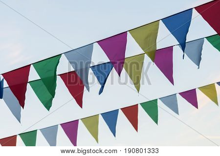 Garland of colorful flags of triangular shape, pennants against blue sky. City street holiday. Modern background, pattern, wallpaper or banner design. Fest, celebration concept
