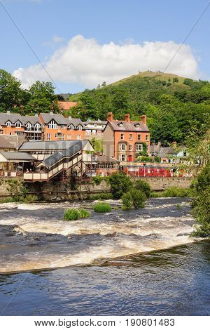 Llangollen Wales UK - June 9 2017: Llangollen with the heritage steam railway station and River Dee and period properties with Dinas Bran castle in the distance