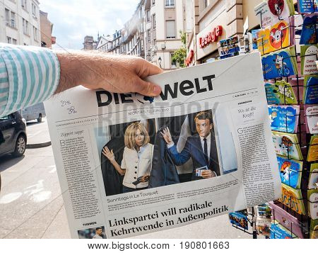 PARIS FRANCE - JUN 12 2017: Man point of view buying at press kiosk Die Welt newspaper with photos of Emmanuel Macron and Brigitte Macron voting for the French legislative election 2017