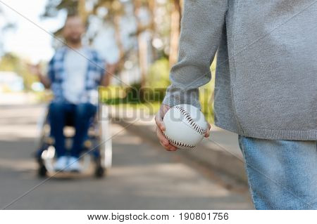 Social security. Male silhouette that sitting on the wheelchair looking at his daughter and trying to catch the ball