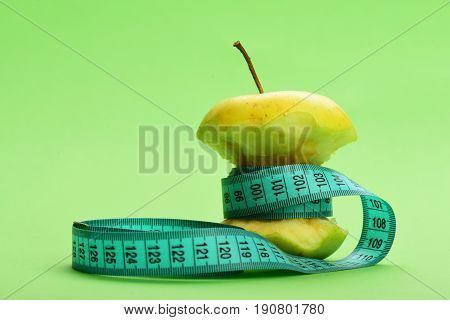 Tape For Measuring In Greenish Blue Color Wraps Around Apple