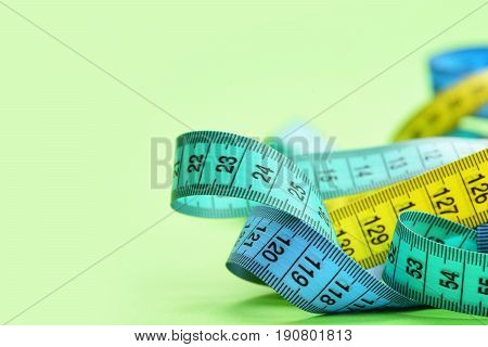 Measure Tapes In Cyan, Blue And Yellow Colors Twisted Disorderly