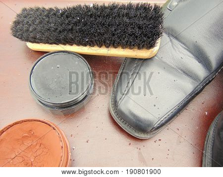 black shiny shoes with shoe polish, shoelaces, a cloth and a brush