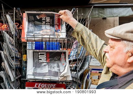 PARIS FRANCE - JUN 12 2017: Man buying at press kiosk French newspaper Aujord'Hui with reactions to French legislative election 2017 a day after first round