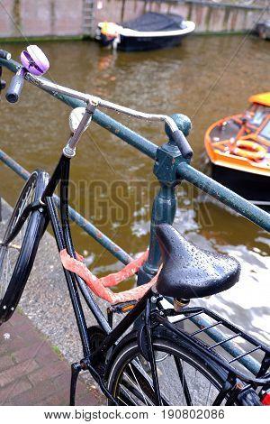 a bicycle padlocked to railings in Amsterdam