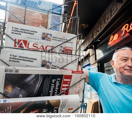 PARIS FRANCE - JUN 12 2017: Senior buying at press kiosk French newspaper with reactions to French legislative election 2017 a day after first round