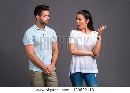 A beautiful young couple standing and arguing in the studio