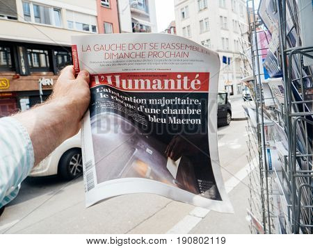 PARIS FRANCE - JUN 12 2017: Man point of view personal perspective buying at press kiosk French newspaper L'Humanite with reactions to French legislative election 2017 a day after first round