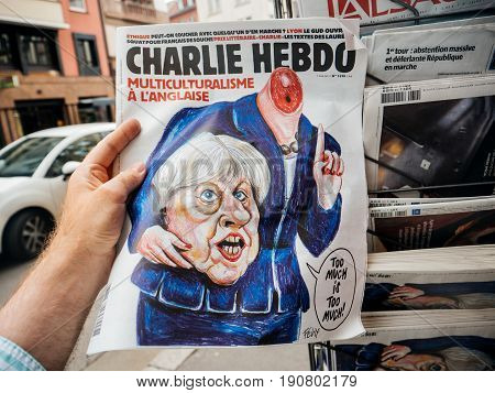 PARIS FRANCE - JUN 12 2017: Man point of view personal perspective buying at press kiosk satire newspaper Charlie Hebdo with Theresa May without head caricature with reactions to United Kingdom general election of 2017 - May fights to remain PM