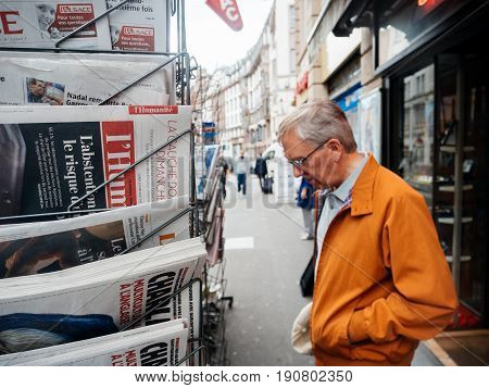 PARIS FRANCE - JUN 12 2017: Senior man buying at press kiosk French newspaper with reactions to French legislative election 2017 a day after first round