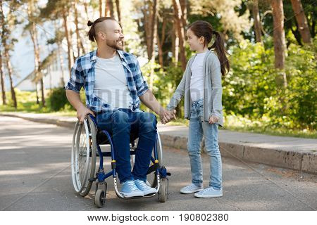 Have a look. Handsome invalid man with stylish haircut sitting on his wheelchair and keeping smile on his face while looking at his daughter