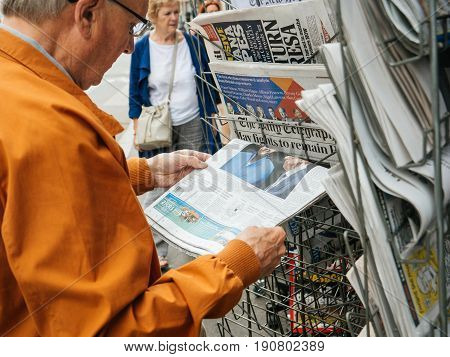 PARIS FRANCE - JUN 12 2017: Senior man buying at press kiosk UK newspaper The Daily Telegraph with Theresa May picture and reactions to United Kingdom general election of 2017