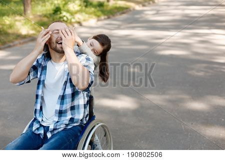 Play hide-and-seek. Positive man sitting on the wheelchair and keeping smile on his face while touching hands of his kid