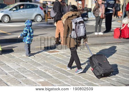 Tourists who just landed, with their travel bag, cross a pedestrian crossing