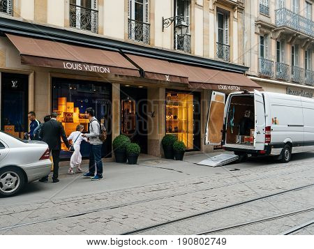 STRASBOURG FRANCE - JUN 12 2017: White delivery van supplying stock with clothes parcels and accessories a windows of the Louis Vuitton store on empty shopping street