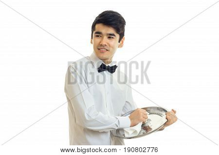 young cute waiter looks sideways smiles and wipes the tray towel isolated on white background
