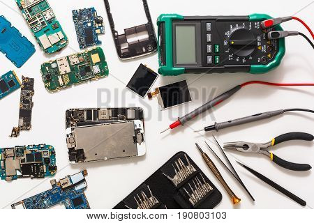 Mobile repair flat lay. Dissasembled smartphone top view. Technician workplace with instruments and cell phone components