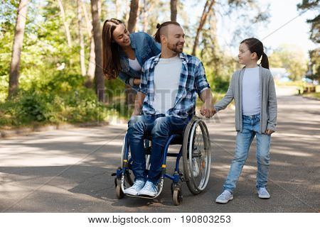 Family day. Smiling invalid man sitting on the wheelchair and holding hands with daughter while expressing positivity