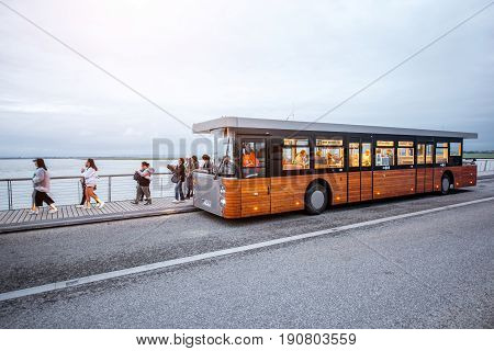 MONT SAINT MICHEL, FRANCE - May 29, 2017: Tourists walk near the famous shuttle bus designed specially for transporting tourists from Caen to Saint Michel abbey