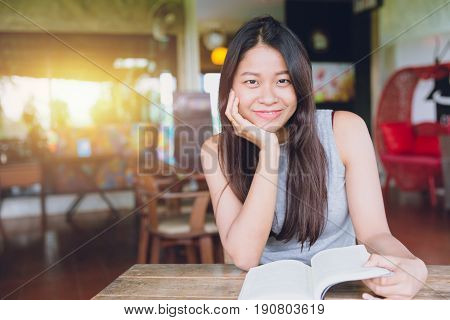 Enjoy relax times with reading book Asian Thai women smile with book in coffee shop.