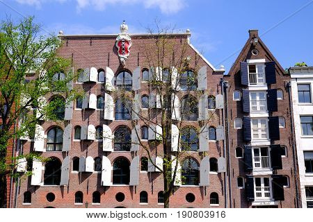 front of large dutch canalside house in amsterdam with shutters