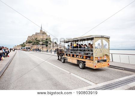 MONT SAINT MICHEL, FRANCE - May 30, 2017: View on the famous Mont Saint Michel island with carriage full of tourists