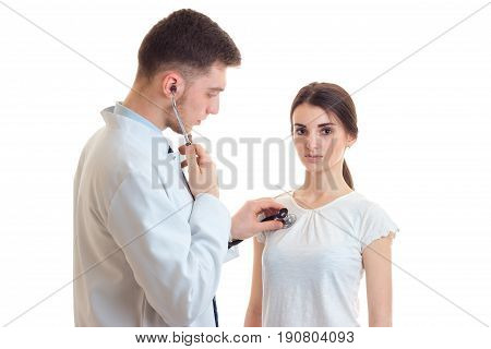 a doctor in a white coat listens to the heart of a young woman close-up isolated on white background
