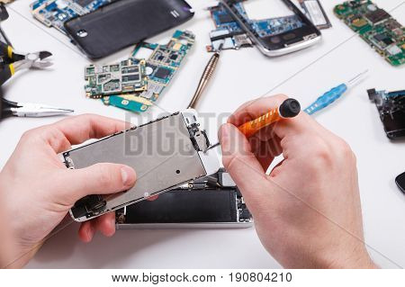 Repairman disassembling smartphone with screwdriver. Technician fixing broken phone, electronics repair service, repairer pov