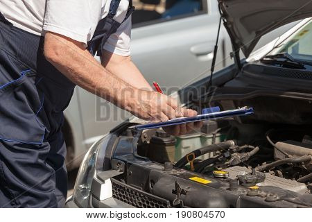 Auto mechanic checking car engine and writing on the clipboard