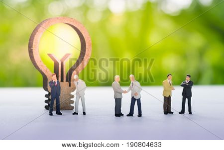 Miniature businessman handshaking with business idea concept using as background commitment agreement investment and partnership concept.